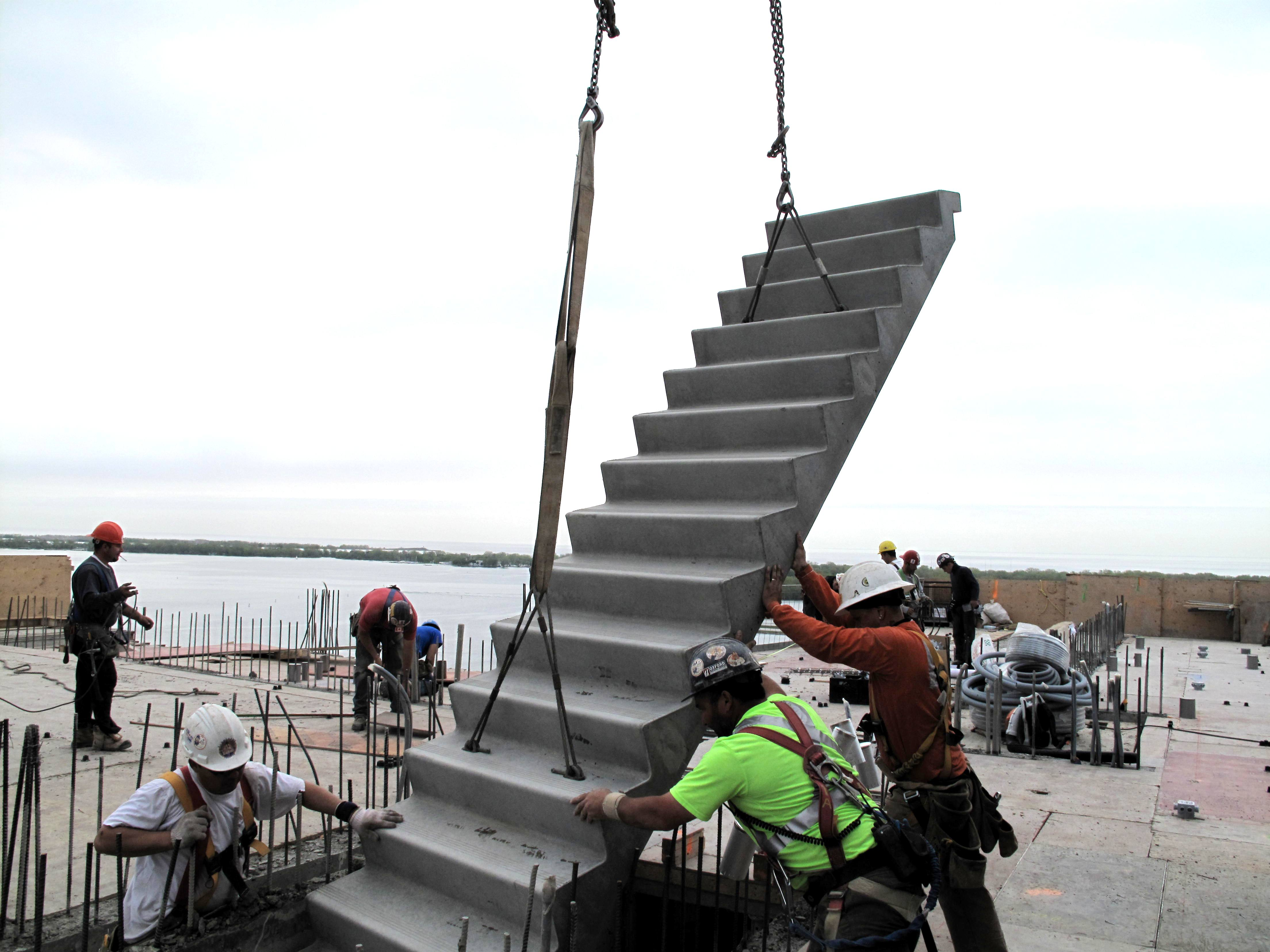 Construction Workers Guiding Precast Concrete Stairs That Are Being Crane Dropped Into Proper Position