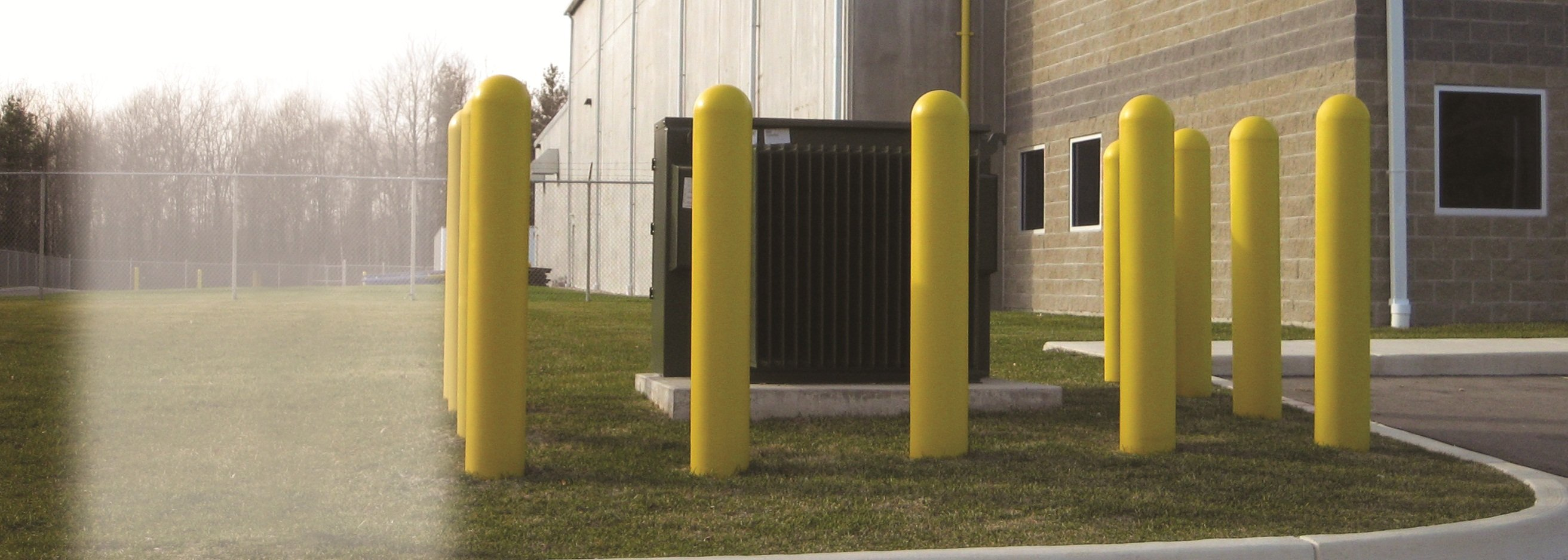 Yellow Precast Concrete Safety Bollards Surrounding Hydro Box